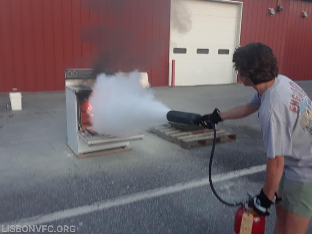 FF/EMT Byrd uses a CO2 extinguisher to  put out the oven fire.